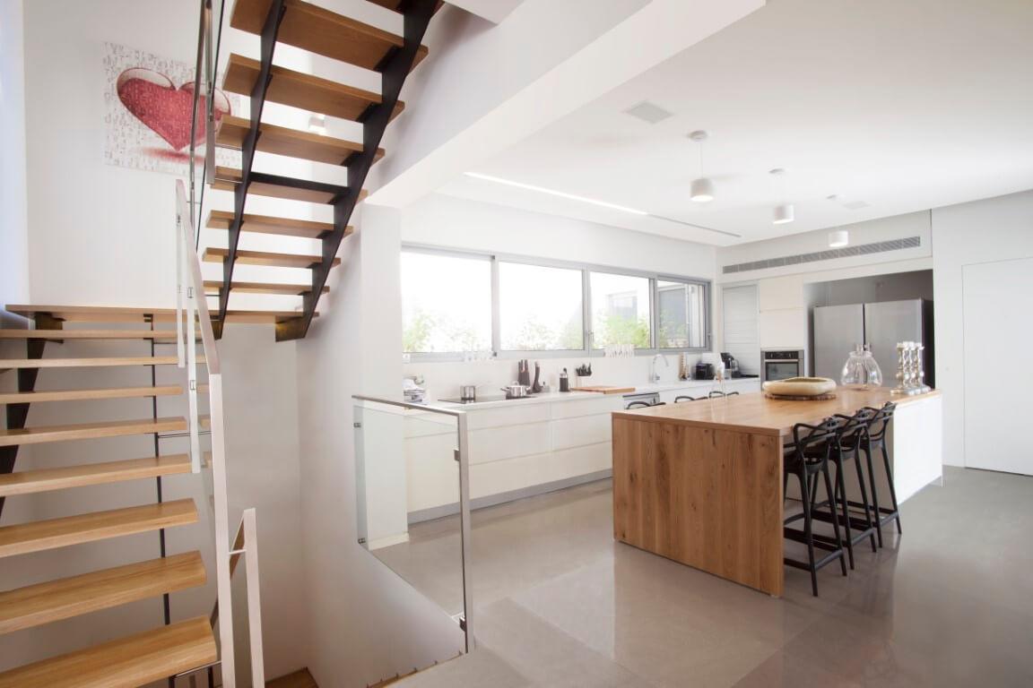 מבט חרב שתופס גם את המטבח וגם את מדרגות הברזל והעץ שעולות אל המפלס העליון