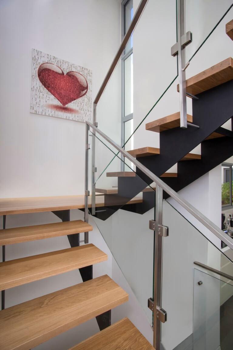 גרם מדרגות העץ הראשון מוביל אל תמונה של לב אדום על הקיר וממשיך לעלות למעלה מלוו במעקה זכוכית