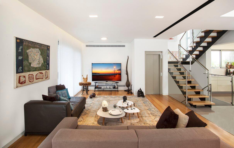 מבט רחב על הסלון ושני גרמי מדרגות הברזל והעץ מימינו
