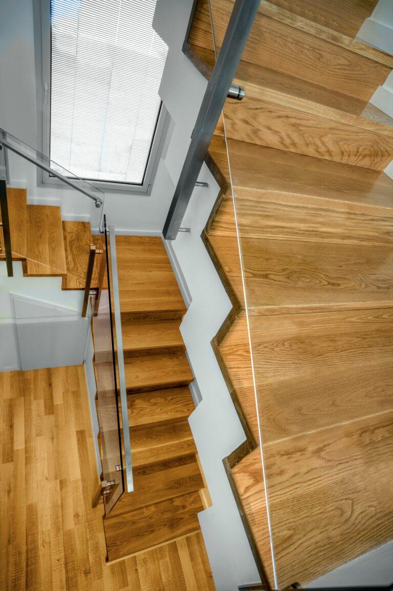 גרם מדרגות עץ אחד עולה למעלה ושניים יורדים למטה אל הפרקט שמתחבר עם מדרגות העץ בהרמוניה