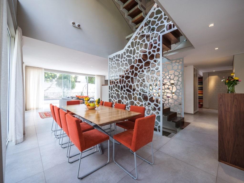 שלושה גרמי מדרגות מרחפות מעץ ספלי עם מעקה זכוכית ליד פינת אוכל בכתום ועץ