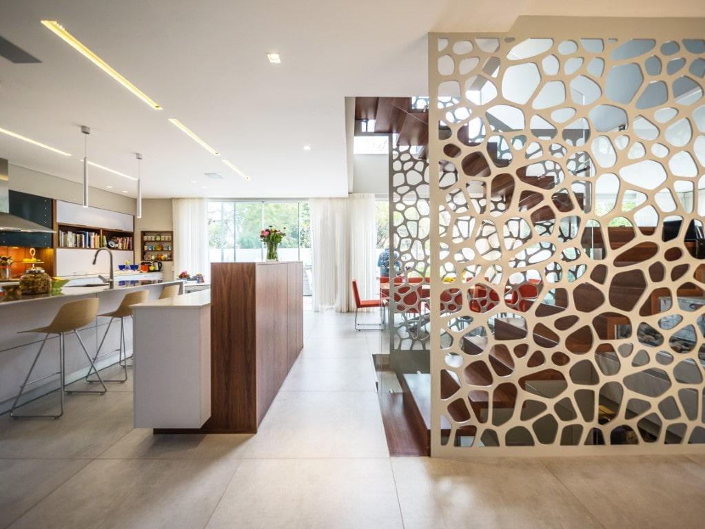 שני גרמי מדרגות צפים מעץ עם ומעקה זכוכית מבעד למחיצות המעוצבות לצד המטבח המפואר