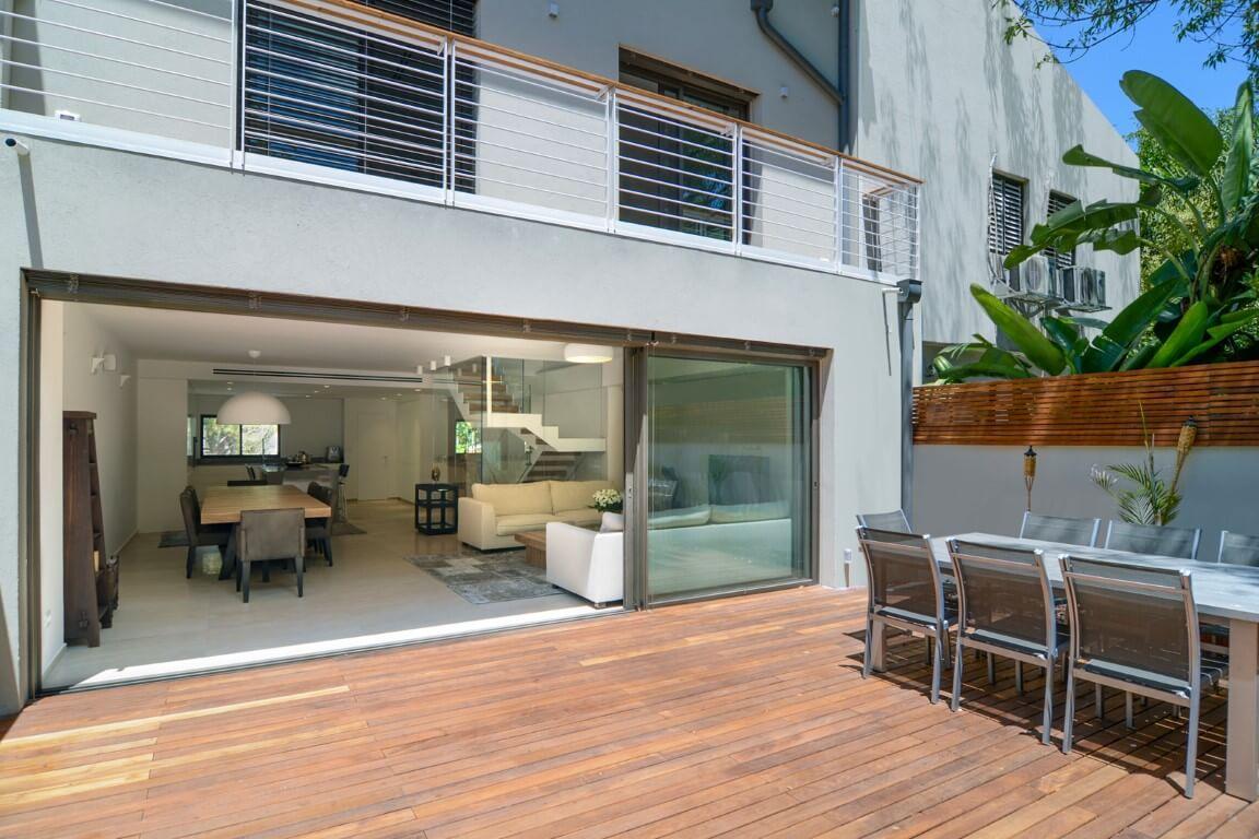 מבט מהגינה אל הסלון ושלושת גרמי מדרגות העץ והברזל הלבן שעולים אל הקומה העליונה