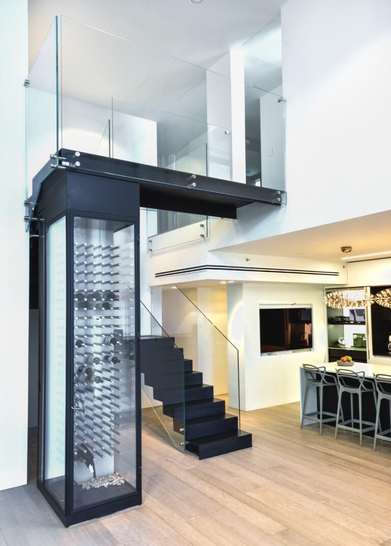 מבט רחב על פינת האוכל, מקרר היינות היוקרתי וקונסטרוקצית המדרגות מברזל שחור ומעקה זכוכית