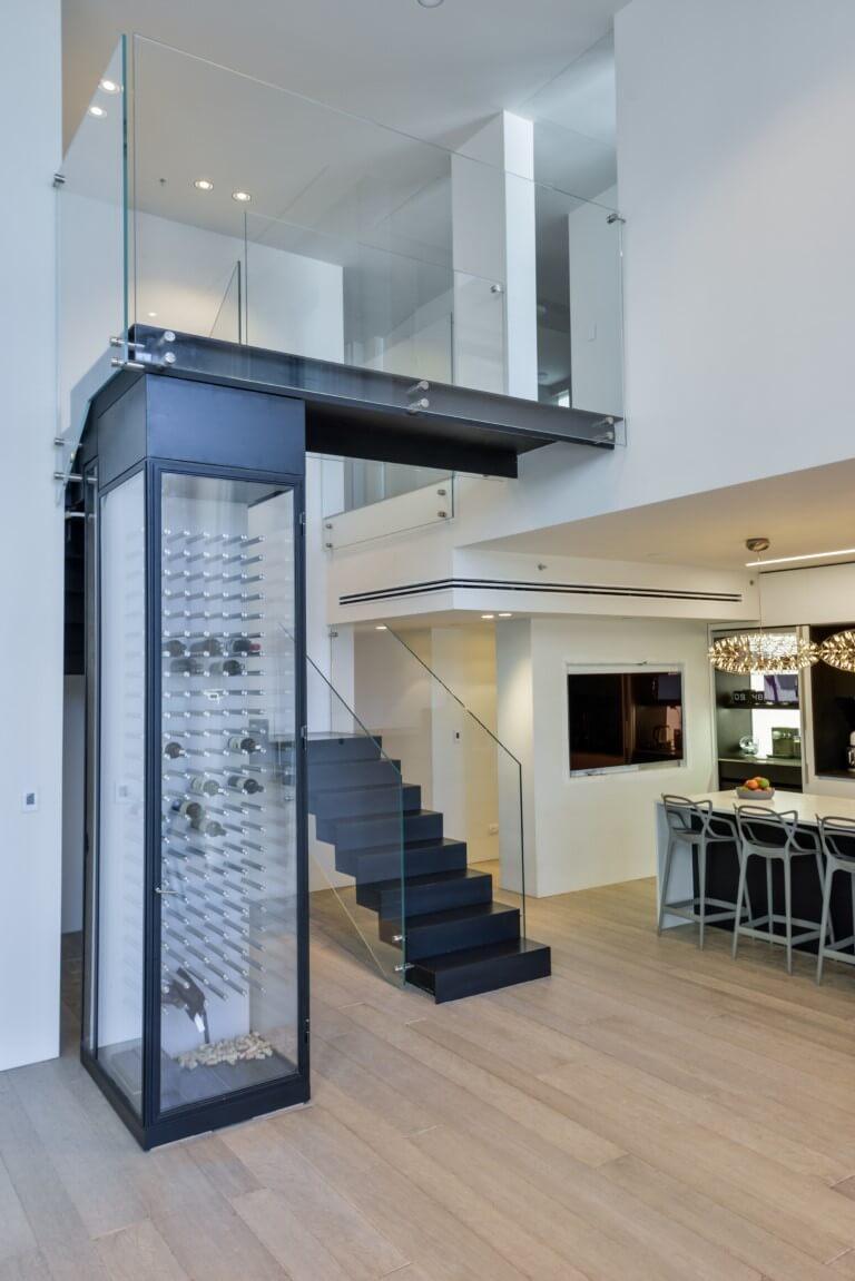 מבט רחב על גרם מדרגות ברזל בשחור עם מעקה זכוכית, מקרר יינות יוקרתי ופינת האוכל