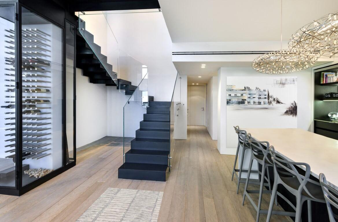 מבט אל המסדרון שמוקף בפינת אוכל ושלושה גרמי מדרגות מברזל שחור עם מעקה זכוכית