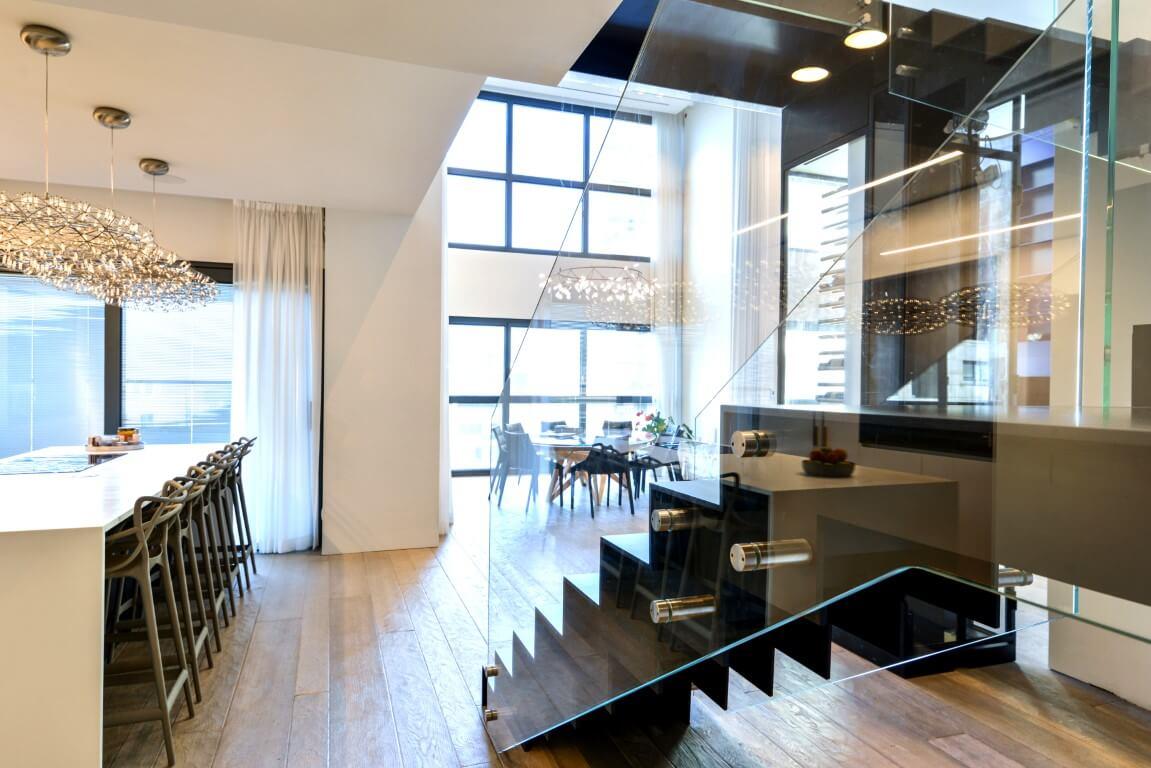 מבט אל הקומה הראשונה של הפנטהאוד המפואר מבעד למעקה הזכוכית של גרם מדרגות הברזל