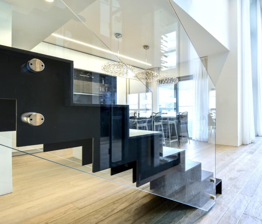 מדרגות ברזל שחור עם מעקה זכוכית על רצפת פרקט עץ בגווני קש וחול מוזהב