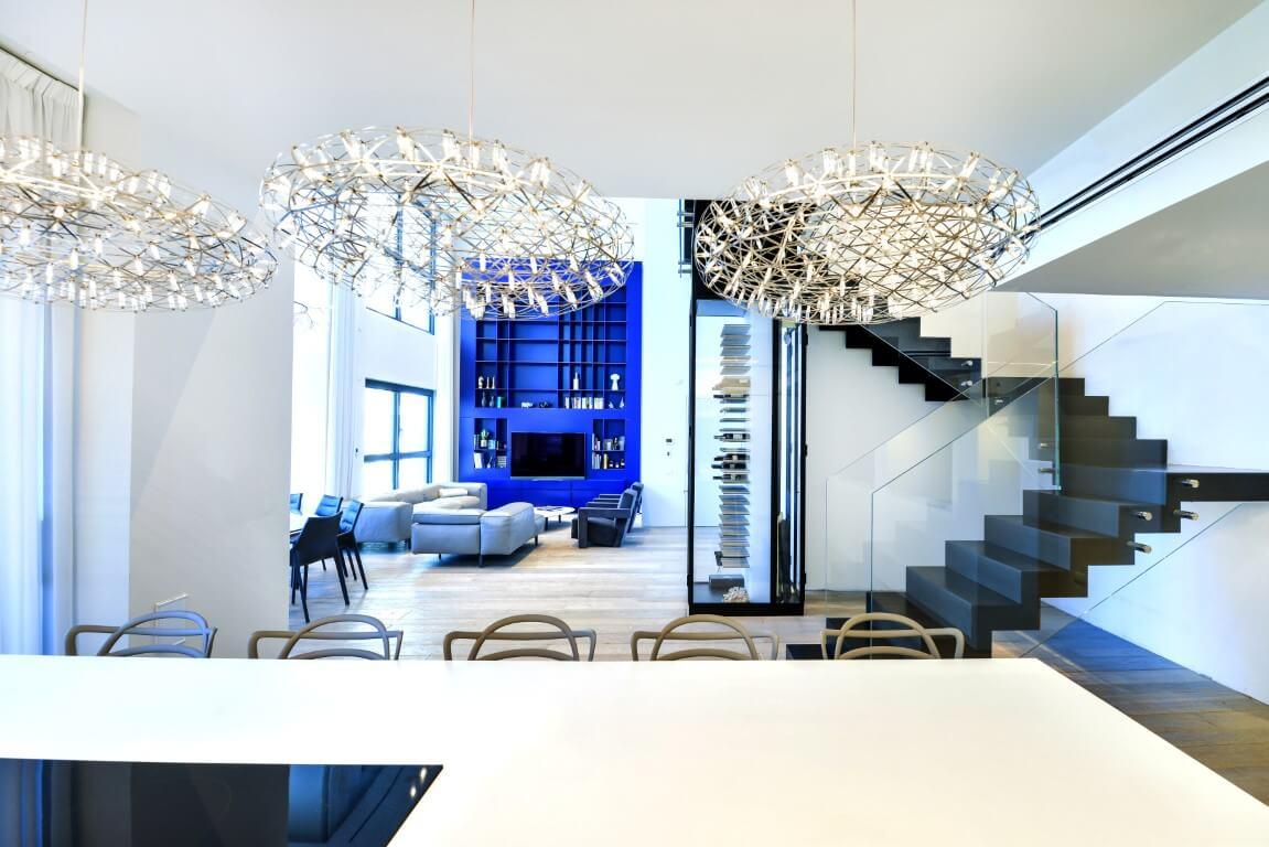 שלושה גרמי מדרגות ברזל מרחפות בשחור עם מעקה זכוכית בין פינת האוכל לסלון הפנטהאוס
