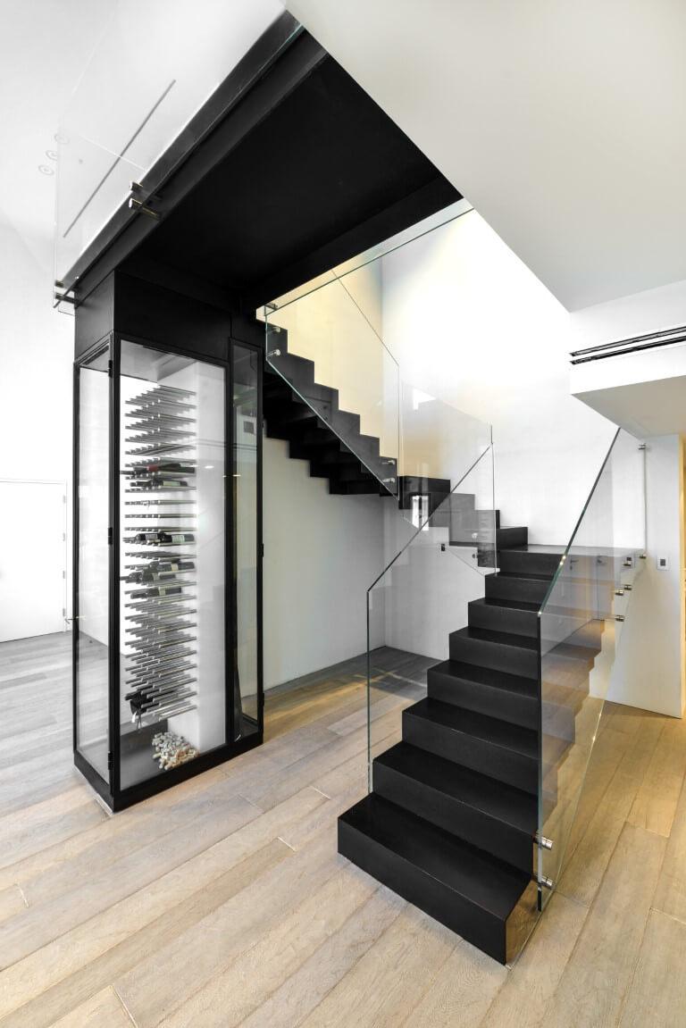 שלושה גרמי מדרגות ברזל שחור עם מעקה זכוכית שקופה בסמוך למקרר היינות