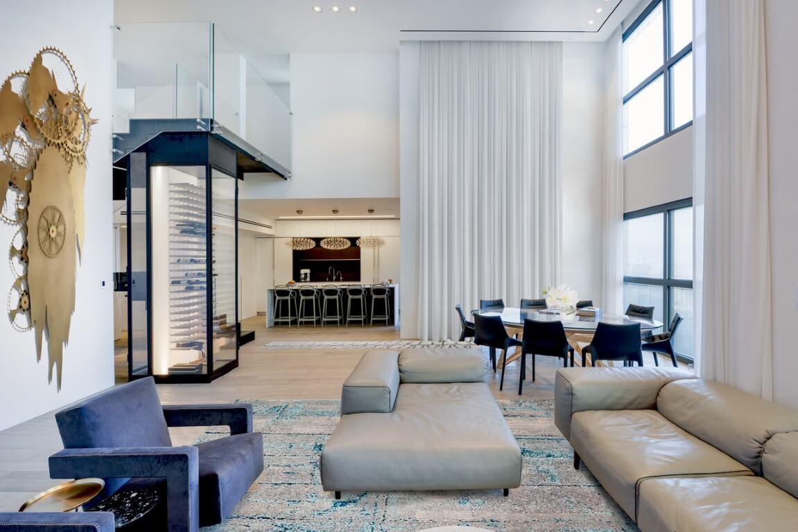 מבט מהסלון המפואר בגווני בז' וכחול אל מקרר היינות, מעקה הזכוכית וקונסטרוקצית הברזל השחור של המדרגות