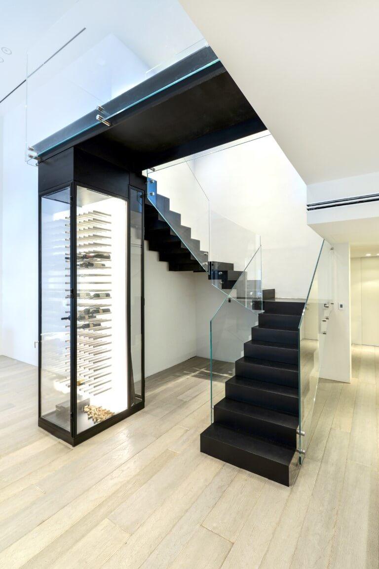 השחור של מדרכי מדרגות הברזל והשקוף של מעקה הזכוכית מתכתבים עם השחור של והזכוכית של מקרר היינות