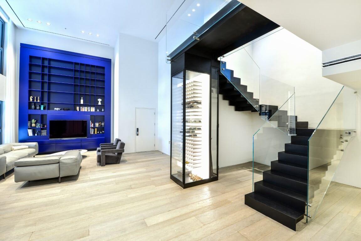 שלושה גרמי מדרגות ברזל שחור עם מעקה זכוכית מתכתבים עם הכחול רואיל של מסגרת החלון בסלון