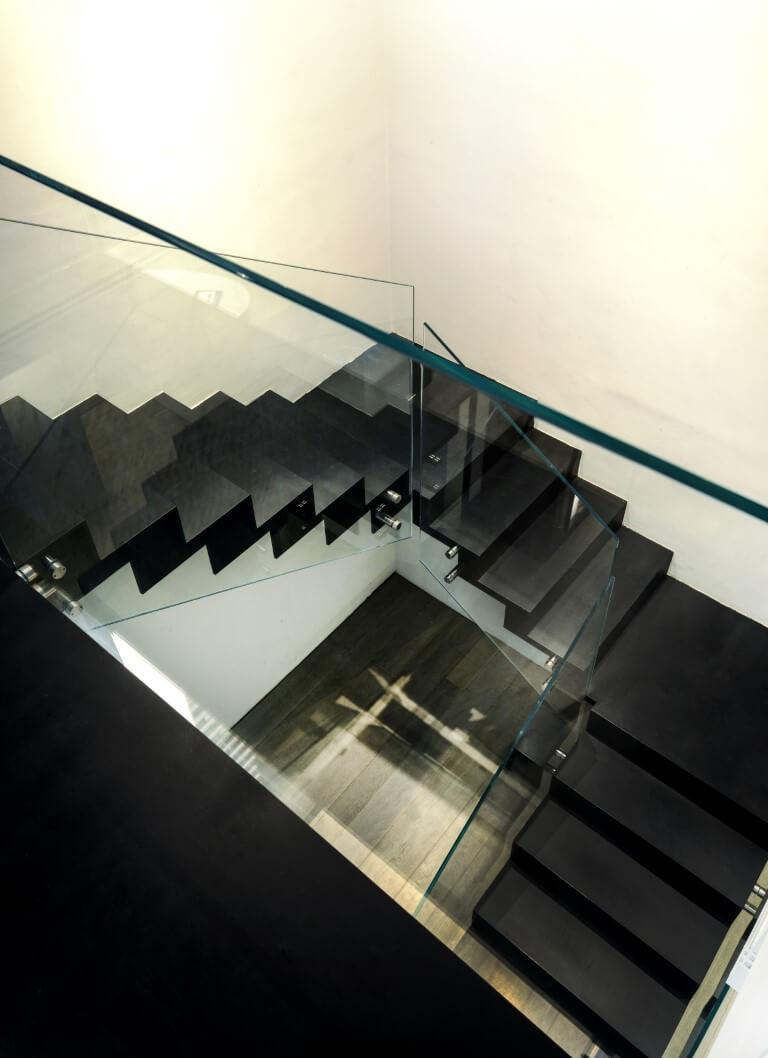 מבט מלמעלה דרך שלושת גמרי המדרגות ברזל שחור עם מעקה זכוכית אל רצפת הפרקט בקומה הראשונה