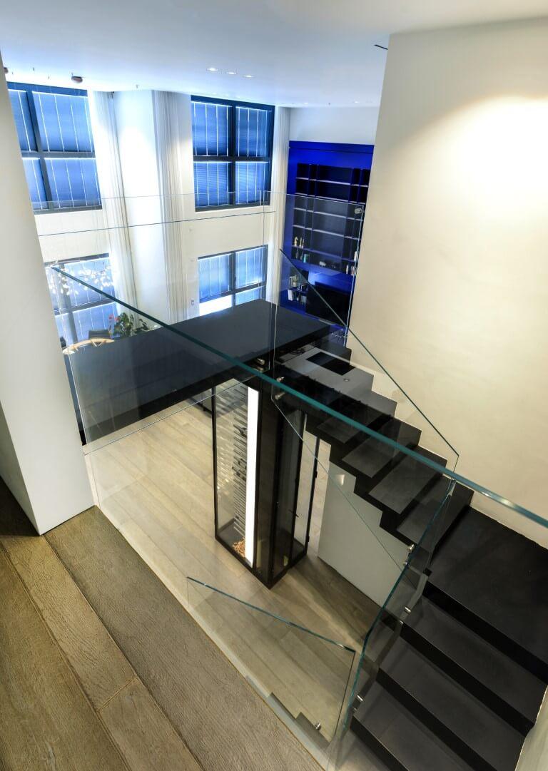 שלושה גרמי מדרגות מברזל שחור ובליווי מעקה זכוכית מחברים בין מפלסי הפנטהאוס