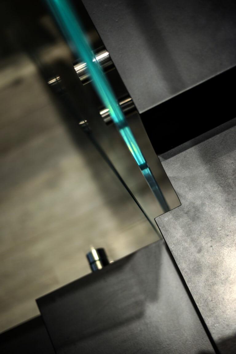 תקריב למעקה הזכוכית והחיבור שלו עם מדרך הברזל השחור