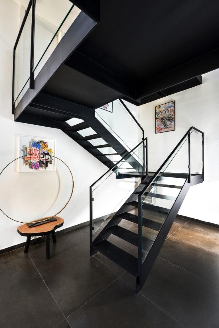 שני גרמי מדרגות מברזל שחור עם מעקה ברזל וזכוכית עולים בליווי של תמונות ופריטי נוי סביב