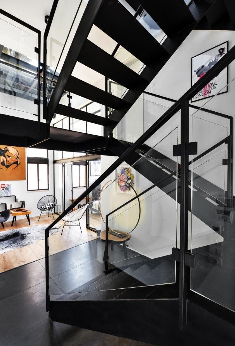 שלושה גרמי מדרגות מברזל שחור בסגנון תעשייתי מחברות בין מפלסי הוילה