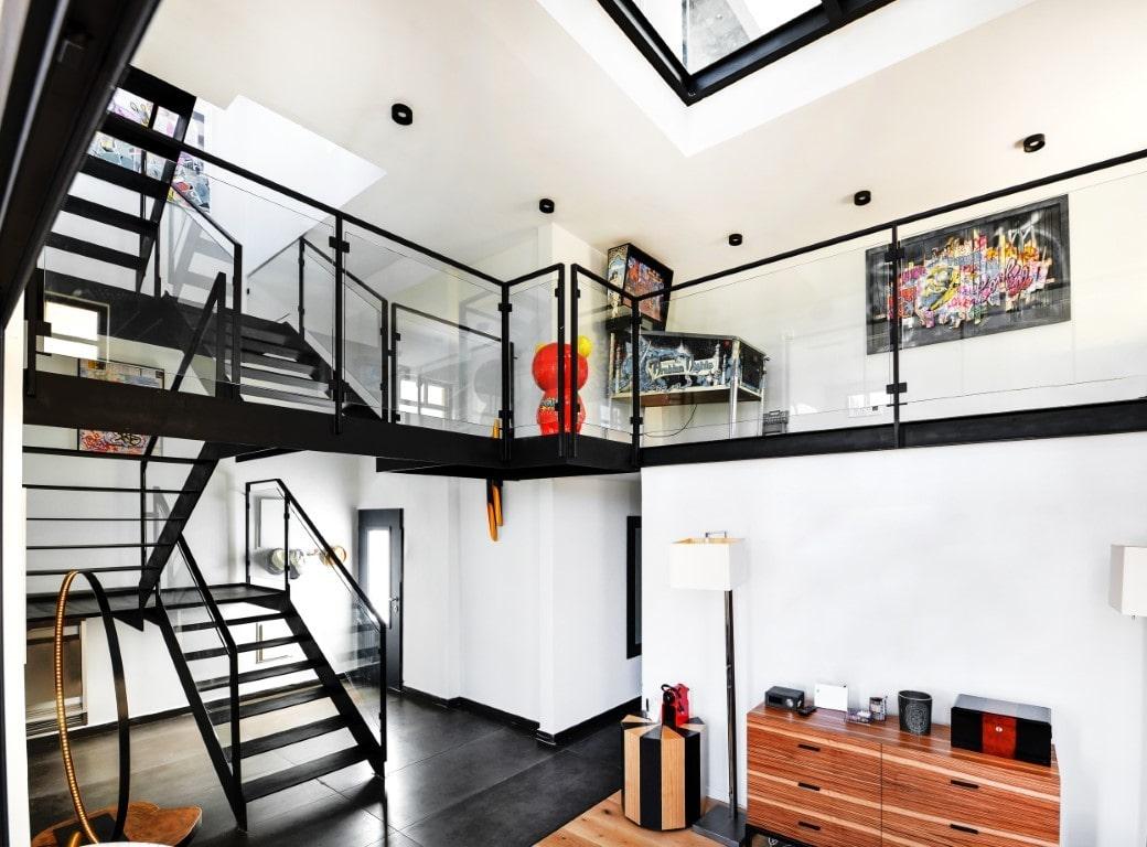 מפלס מברזל שחור משולב מדרגות ברזל שמחברות ביו שתי קומות עם הגלריה במרכז