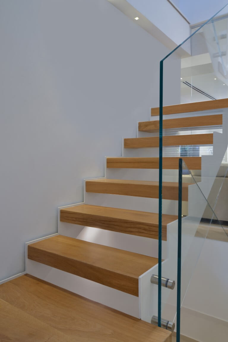 תקריב על קונסטרוקצית הברזל הלבנה שמחזיקה מדרגות עץ אלון בגוונים של חימר קדרים ונחושת מיושנת ומלווה במעקה זכוכית