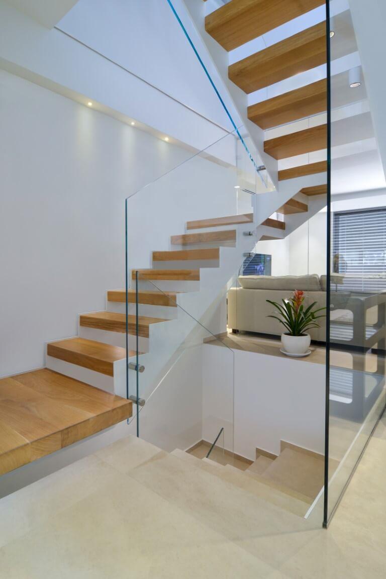 שלושה גרמי מדרגות מברזל לבן ועץ אלון עולים אל המפלס העליון מוקפים במעקה זכוכית שקופה
