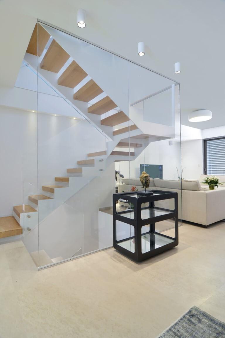 פיר מדרגות הברזל והעץ מוקף כמעט כולו במחיצת זכוכית בגובה התקרה שמהווה גם מחיצה שמפרידה בין המדרגות לסלון