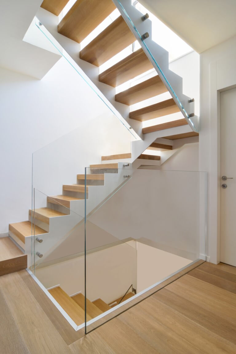 שלושה גרמי מדרגות ברזל ועץ אלון עולים דרך פיר המדרגות אל הקומה העליונה