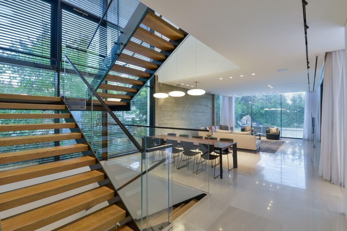 שני גרמי מדרגות עץ בנויים בתוך קונסטרוקצית ברזל מחברים את קומת הקרקע עם הקומה העליונה