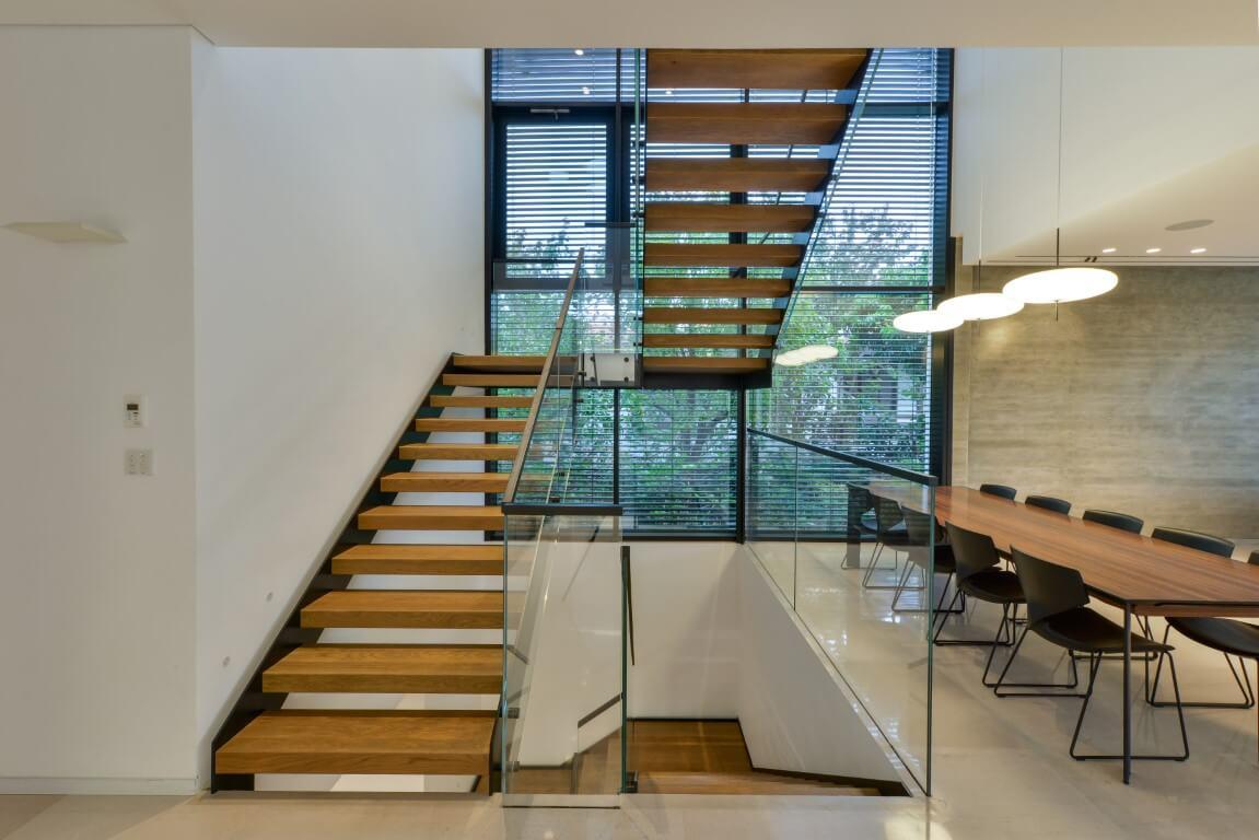 שלושה גרמים של מדרגות עץ מחברים את קומת הקרקע עם המרתף והקומה העליונה בליווי של מעקה זכוכית בטיחותי