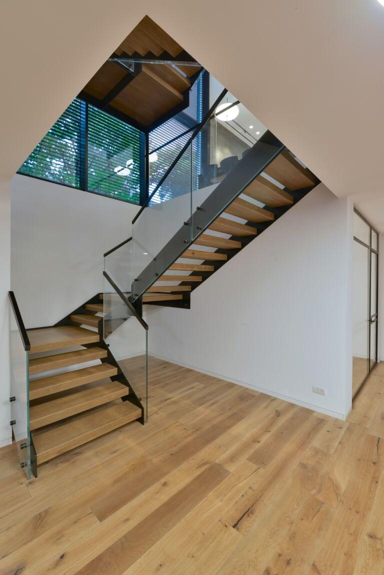 שני גרמי מדרגות שיורדות מקומת הקרקע אל המרתף ומתחברות אל הפרקט הבהיר