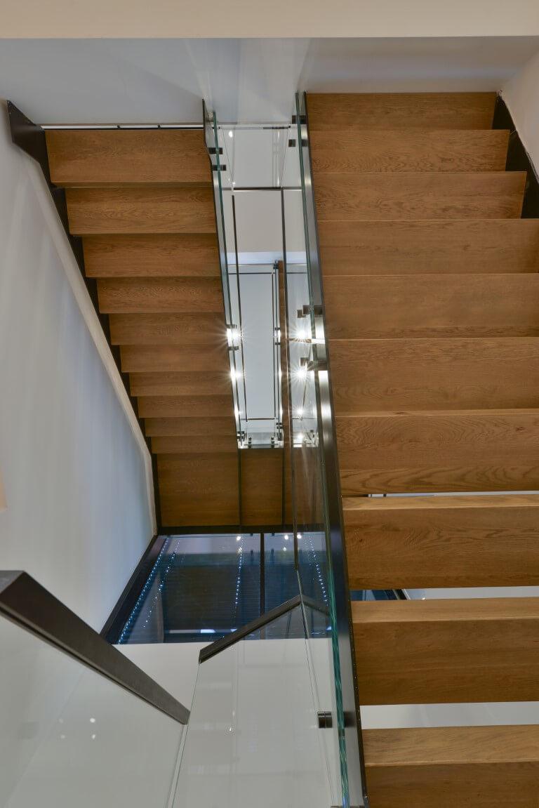 מדרגות קונסטרוקציות ברזל כפולה עם מדרכי עץ בגוונים בהירים במבט מלמטה