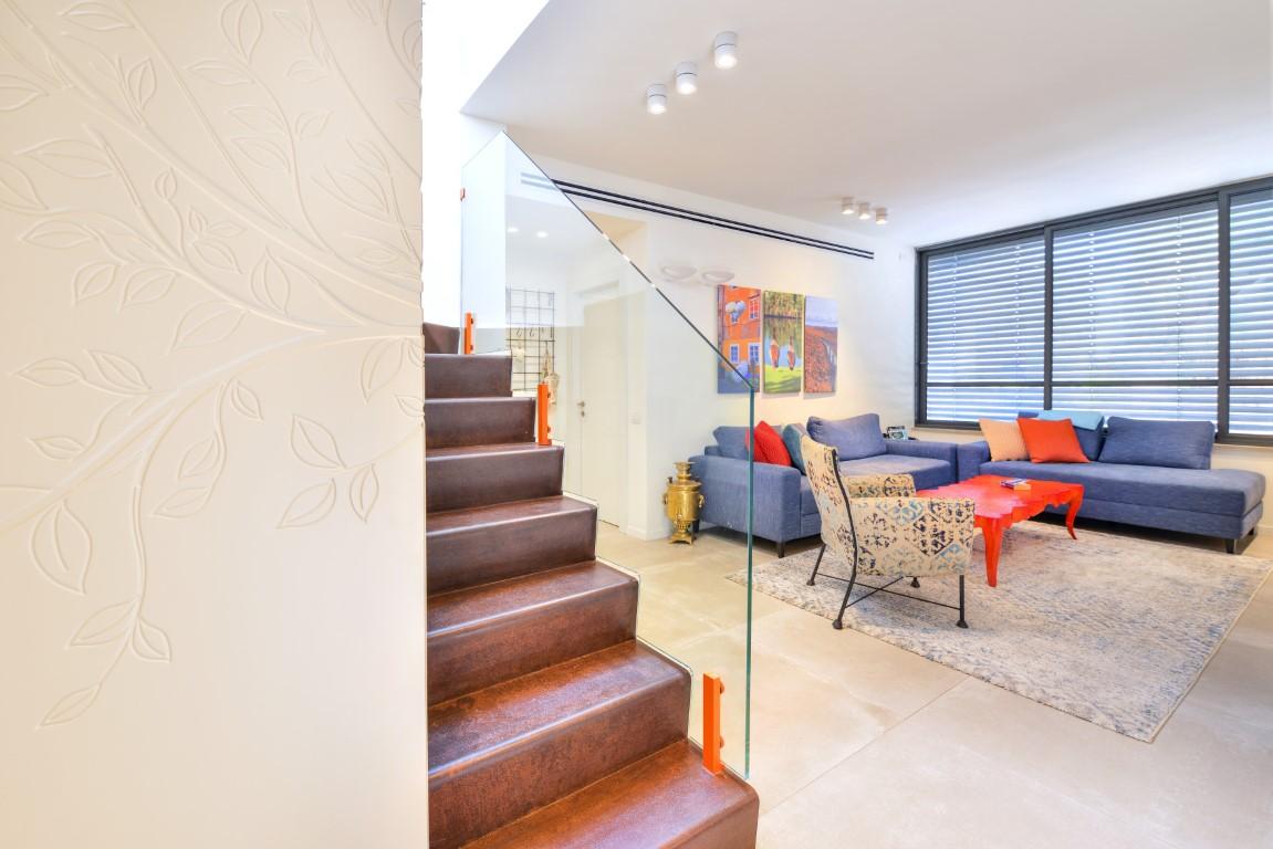 מדרך ברזל ומעקה זכוכית מרכיבים את המדרגות שעולות מהסלון לקומה השניה
