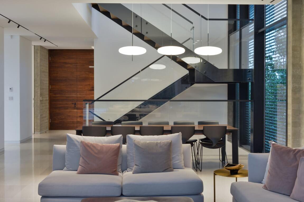 מבט צד על קונסטרוקצית הברזל השחור ומעקה הזכוכית של המדרגות שעולות מקומת הקרקע אל הקומה השניה בוילה