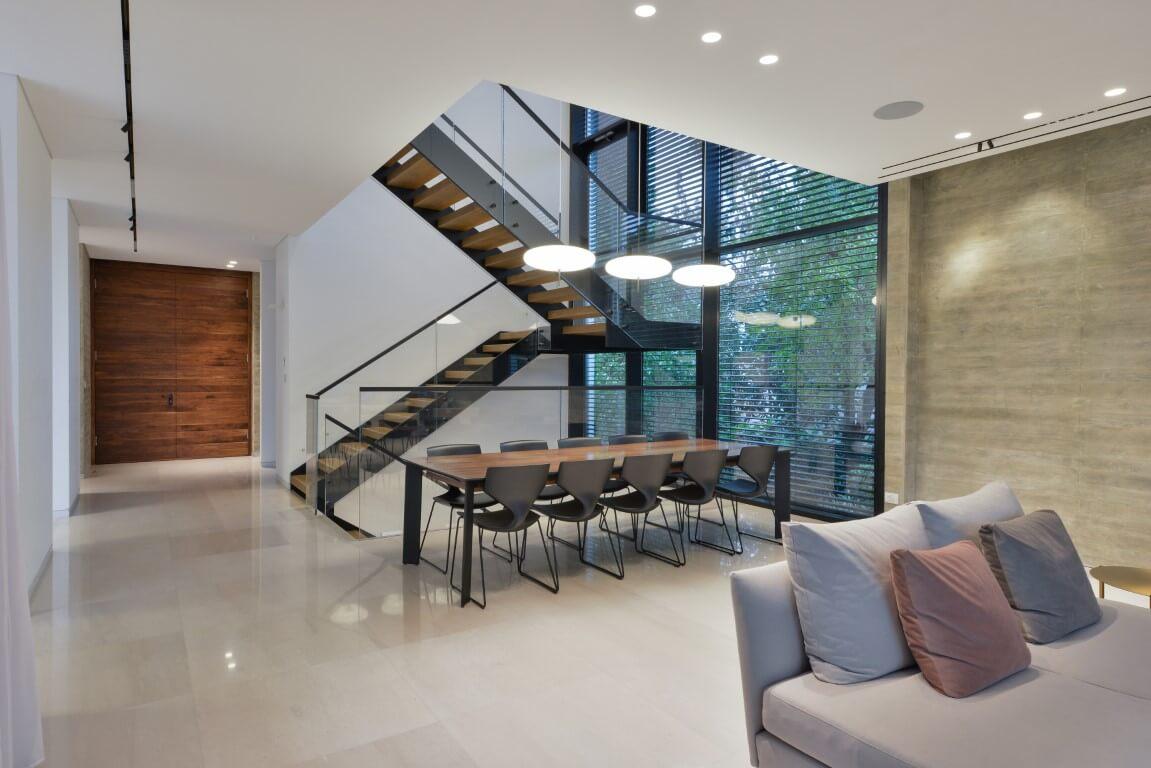 מדרגות ברזל שחור עם מעקה זכוכית ומדרכי עץ ליד פינת האוכל