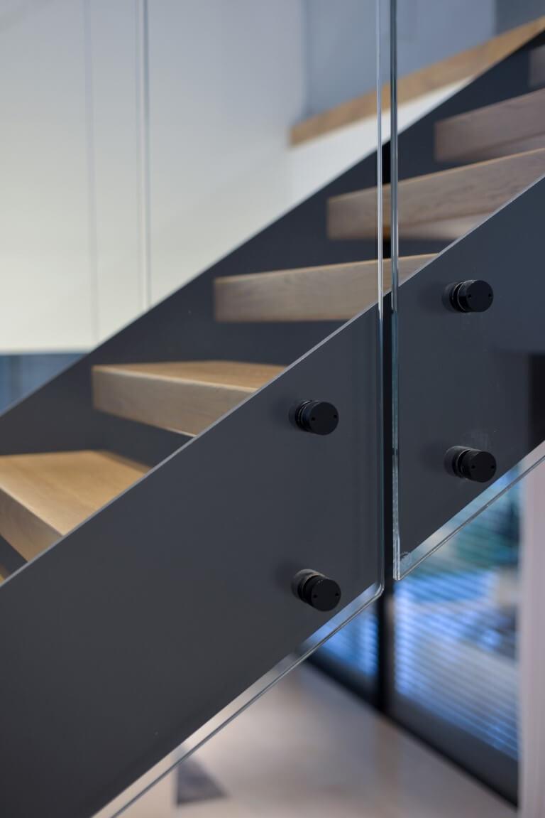 תקריב אל קונסטרוקצית הברזל השחור והחיבורים שלה עם מעקה הזכוכית