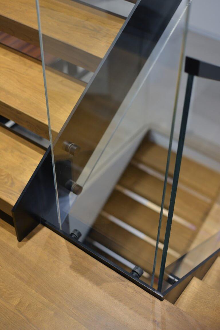 פיר המדרגות מבעד למעקה הזכוכית על רקע מדרכי העץ הבהיר