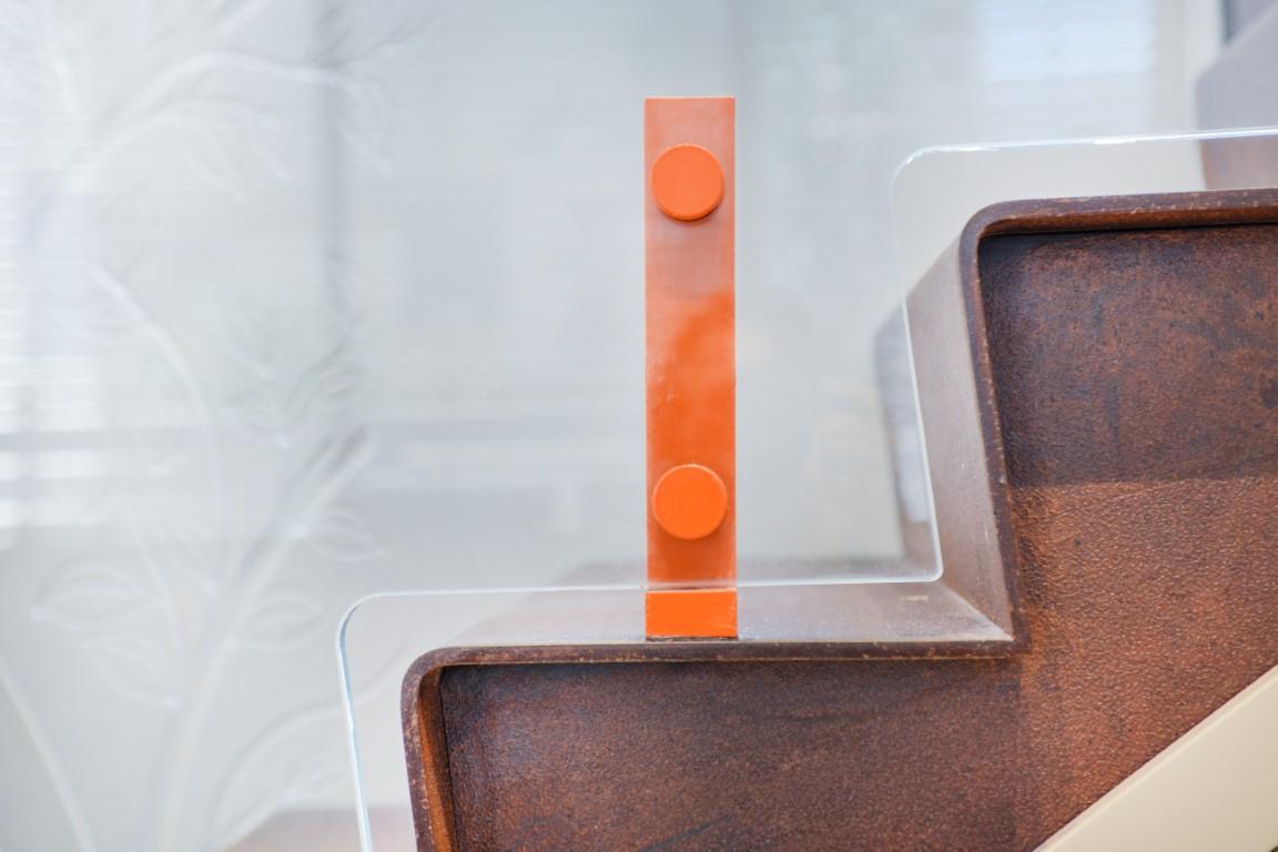 מדרגת ברזל שמחוברת עם מעקה הזכוכית