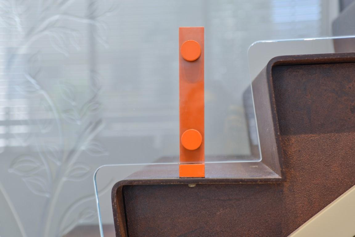 תקריב של חיבורי מעקה הזכוכית עם מדרכי הברזל של המדרגות