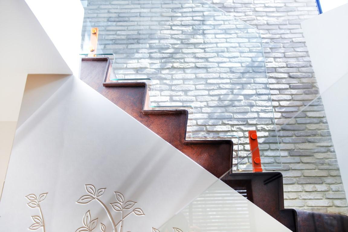 גרם מדרגות ברזל עולה לאורכו של קיר בריקים לבן