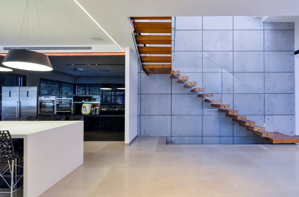 שני מדרכי מדרגות מרחפות מעץ אלון כהה עם מעקה זכוכית על קיר אריחי בטון בכחול סלע