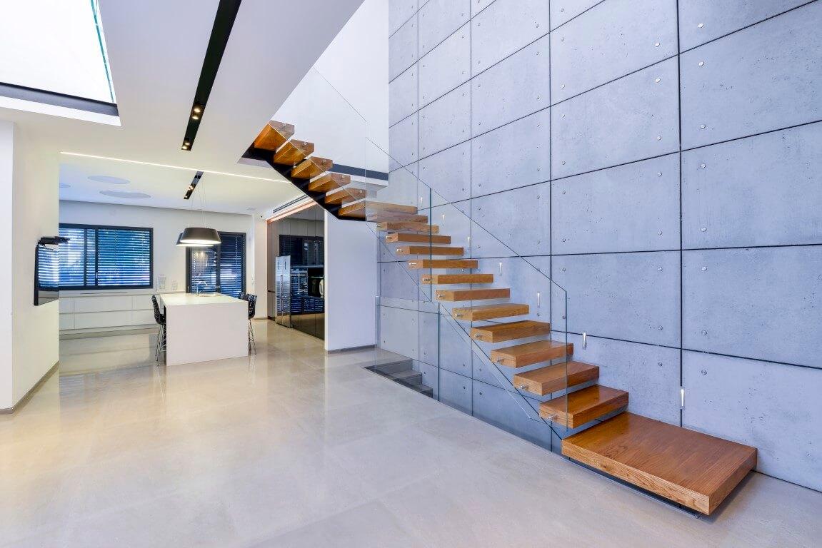 שני גרמי מדרגות צפות ארוכים מעץ אלון חמים עולים אל המפלס העליון בסמוך לקיר פלטות בטון