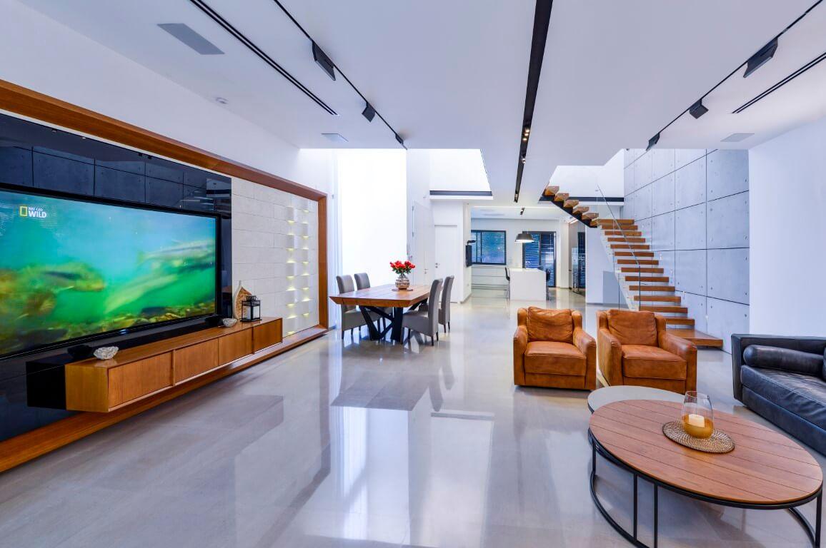 מבט מהסלון המפואר אל פינת האוכל ושני גרמי מדרגות מרחפות מעץ אלון