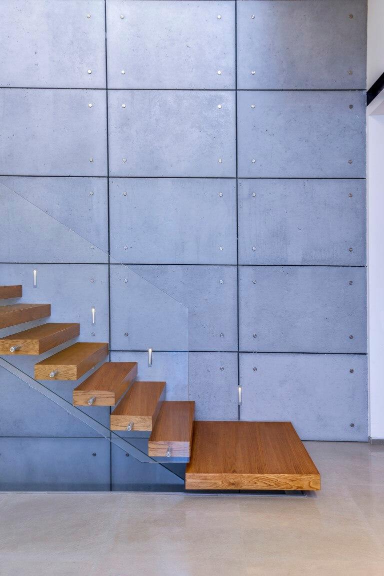 המדרגה הראשונה רחבה יותר וממנה עולות עוד שבעה מדרגות עץ אלון בליווי של מעקה זכוכית