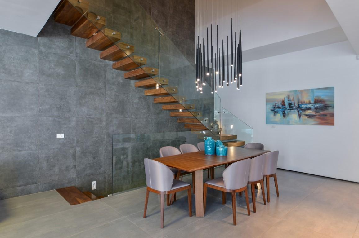 גרם מדרגות צפות מעץ אגוז על רקע קיר כהה ליד פינת האוכל