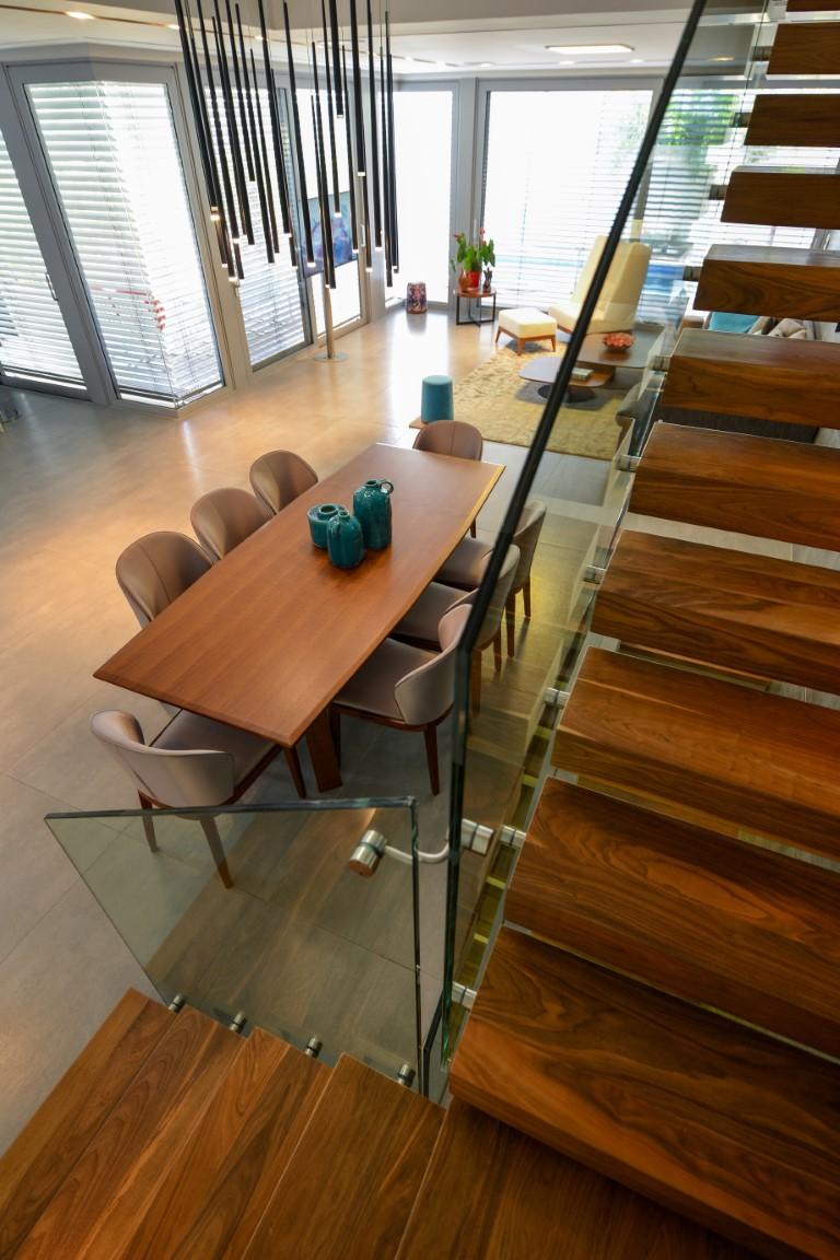 מבט מגרם מדרגות העץ דרך מעקה הזכוכית אל שולחן האוכל