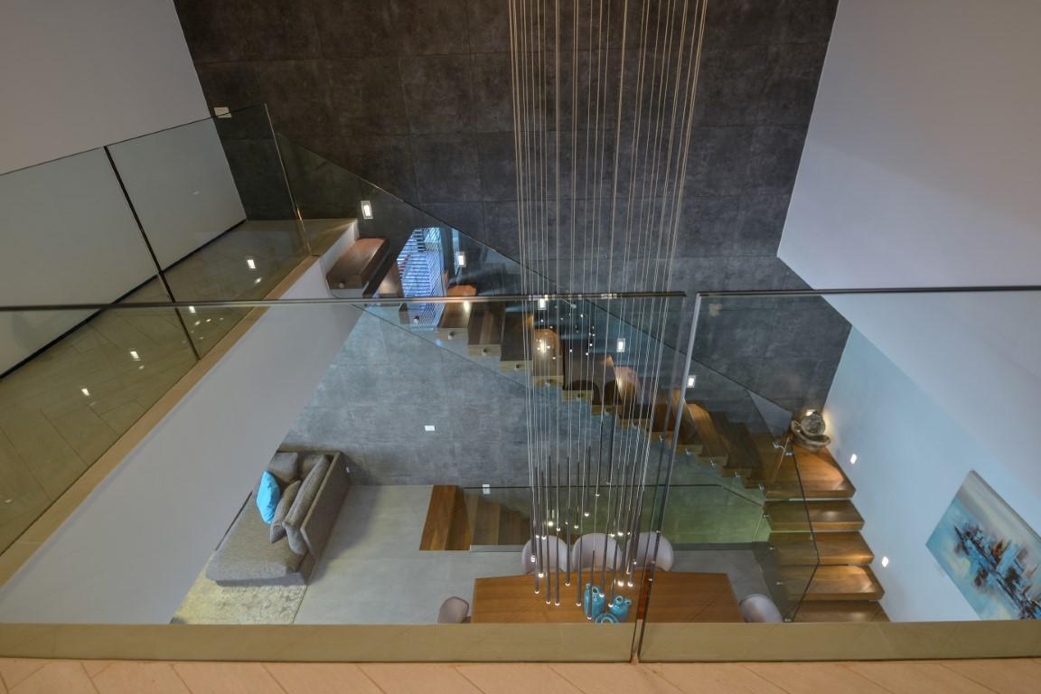 מבט דרך מעקה הזכוכית על שני גרמי מדרגות העץ הצפות מהקומה השניה