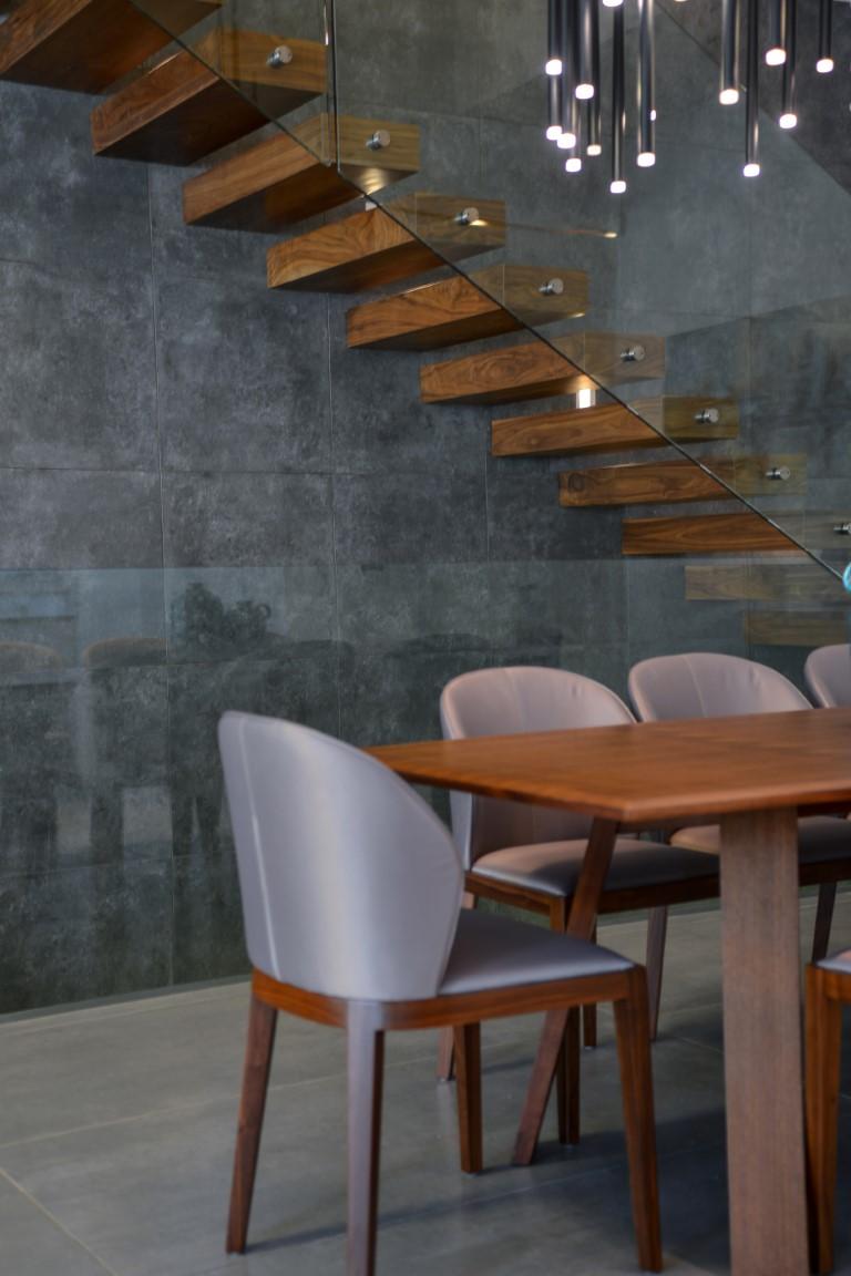 פינת אוכל עם שולחן עץ וכיסאות באפור על גרם מדרגות עץ אגוז שעולה למעלה לאורך הקיר התעשייתי