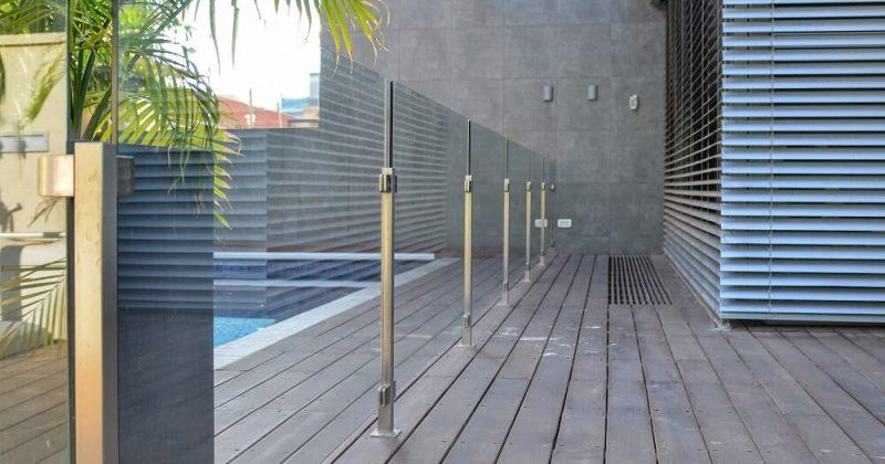 מעקה זכוכית עם עמודי נירוסטה על הדק סביב הבריכה