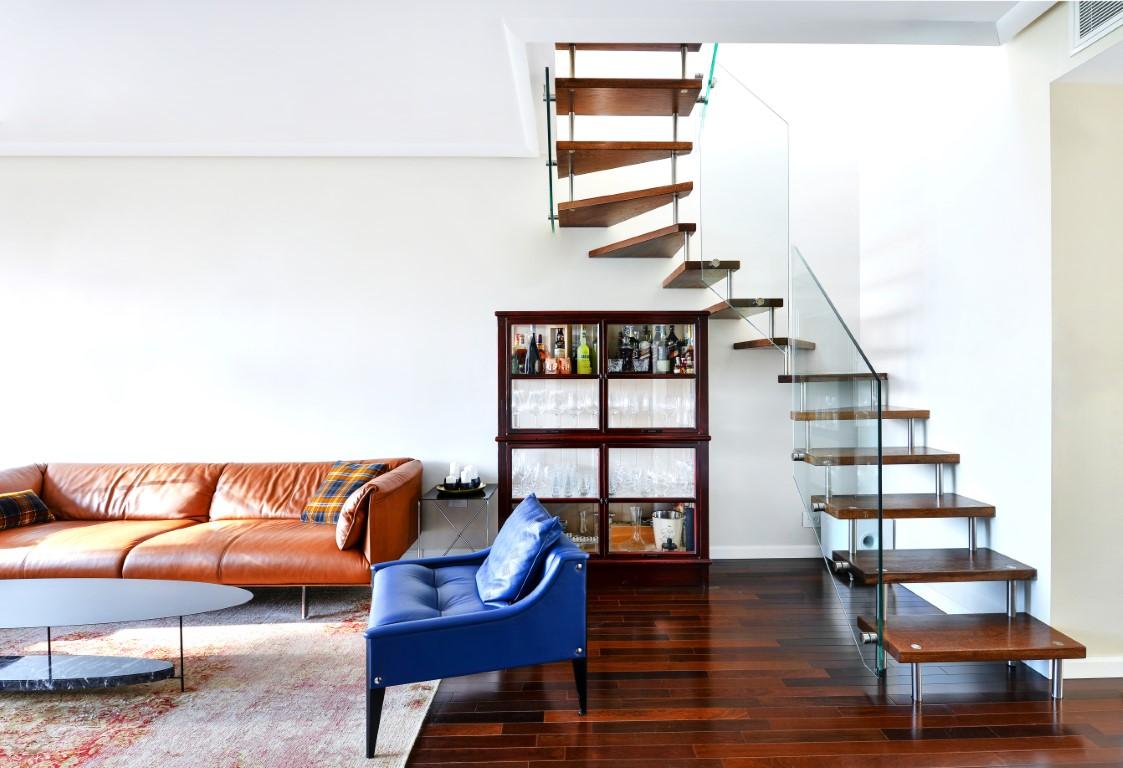 מדרגות עץ אלון מרחפות עם חוצצי נירוסטה ומעקה זכוכית בפינת הסלון המפואר