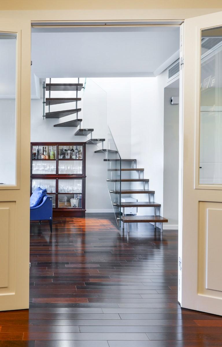 פוקוס על מדרגות העץ הצפות מבעד לדלתות העץ בלבן